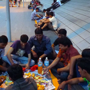 Bangladeshi Muslim migrant men breaking fast along a path to Boon Lay MRT station while commuters continue their journey from work. (Photo: Junjia Ye)