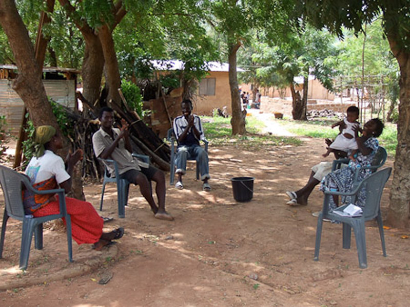 Deaf people chatting under the trees. (Photo: Annelies Kusters)