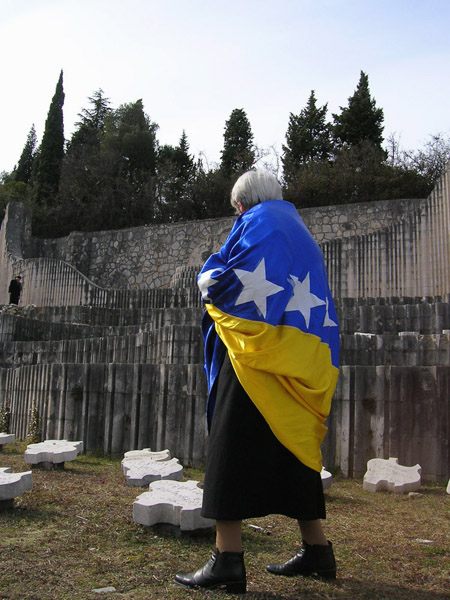 Female former Partisan wrapped in the new Bosnian national flag during a commemoration ceremony at the Partisan Cemetery, Mostar, Bosnia and Herzegovina. (Photo: Monika Palmberger)