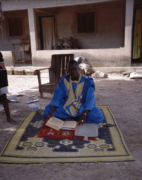 Marabout presenting his Quran and a wooden board with a sura as insignia of his status (Côte d'Ivoire). (Photo: Boris Nieswand)