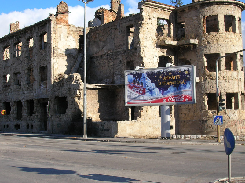One of the numerous buildings on the former frontline destroyed during the war. In its front billboard ad by Coca Cola Seasons Greetings, Mostar, Bosnia and Herzegovina. (Photo: Monika Palmberger)