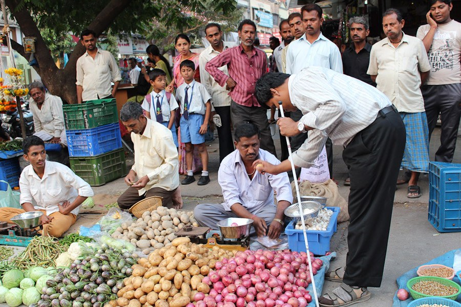 Pradip, who is deaf-blind and one of the research participants, buying vegetables and gesturing with the vegetable seller. (Photo: Annelies Kusters)