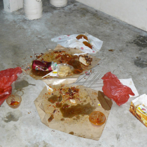Remnants of a take-away dinner left behind on the void deck floor of a block of public housing (HDB) flats. Low wage South Asian migrants housed in nearby worker dormitories are typically held responsible for such use of public space. Littering is an offence that carries a heavy penalty in the high policed city-state of Singapore. (Photo: Laavanya Kathiravelu)