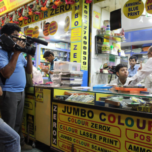 Rohan recording communication between a deaf businessman and a shop owner, Sujit observing the interaction. (Photo: Annelies Kusters)