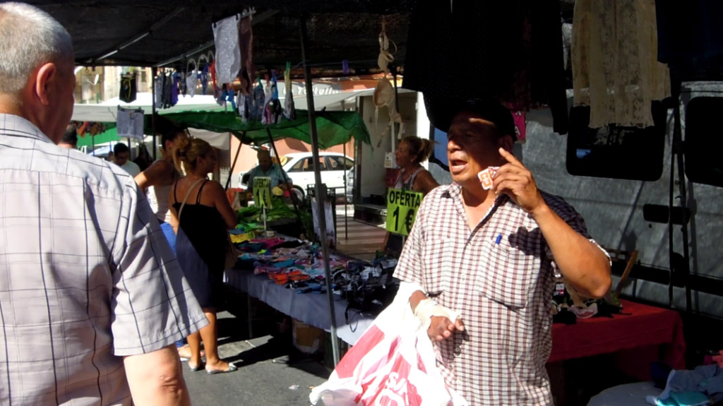 Street market VII. Evangelist street preacher attracting the attention of people [Freeze-frame], Murcia, Spain. (Photo: Damian Omar Martinez)