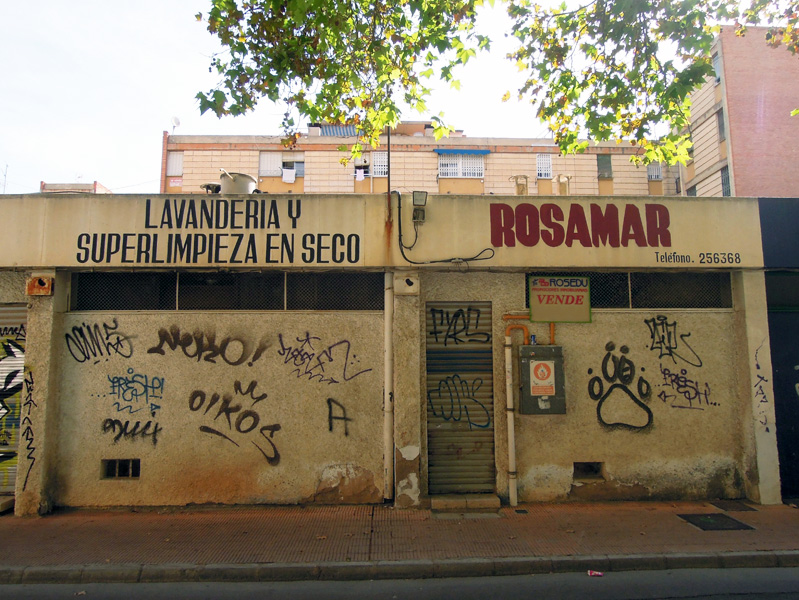 Closed shops in former commercial area with social housing blocks behind, multi-ethnic neighborhood, Murcia, Spain. (Photo: Damian Omar Martinez)