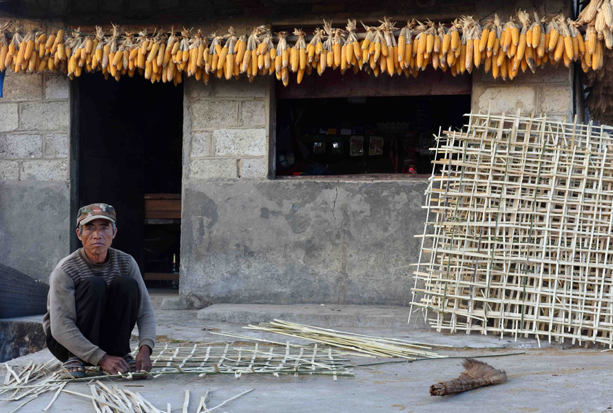 A local man intertwines split bamboo strips into a fence-like structure in front of a small shop outside his home. (Photo: Naomi Hellmann)