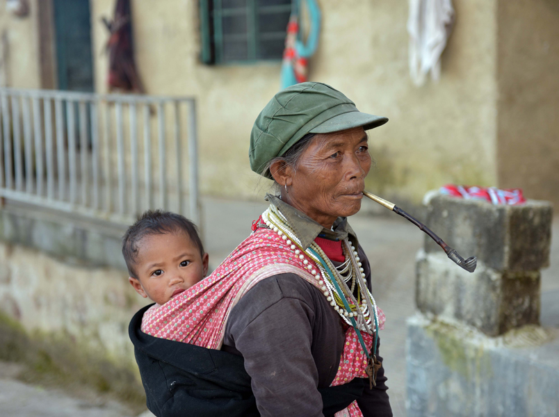 A village woman, smoking tobacco from a traditional long pipe and wearing amulets around her neck, carries a young child on her back. Children typically remain in the care of elderly extended family while their parents migrate out to distant coastal provinces for work. (Photo: Naomi Hellmann)