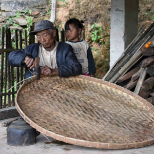 A young girl observes an elderly man fasten the rim of an open, circular, shallow, handwoven bamboo receptacle used for drying crops such as grain, tea, tobacco, fruits, spices, nuts, beans, and seeds on. (Photo: Naomi Hellmann)