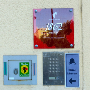 "Entrance to the Julius Meinl company in Julius-Meinl-Gasse, which became one of the most important coffee manufacturer and retailer during the Habsburg Monarchy. A sticker of the initiative ""Mein Julius"" ('My Julius') challenges the racial stereotypes of the company's logo depicting a black child servant wearing a fez. (Photo: Annika Kirbis)"