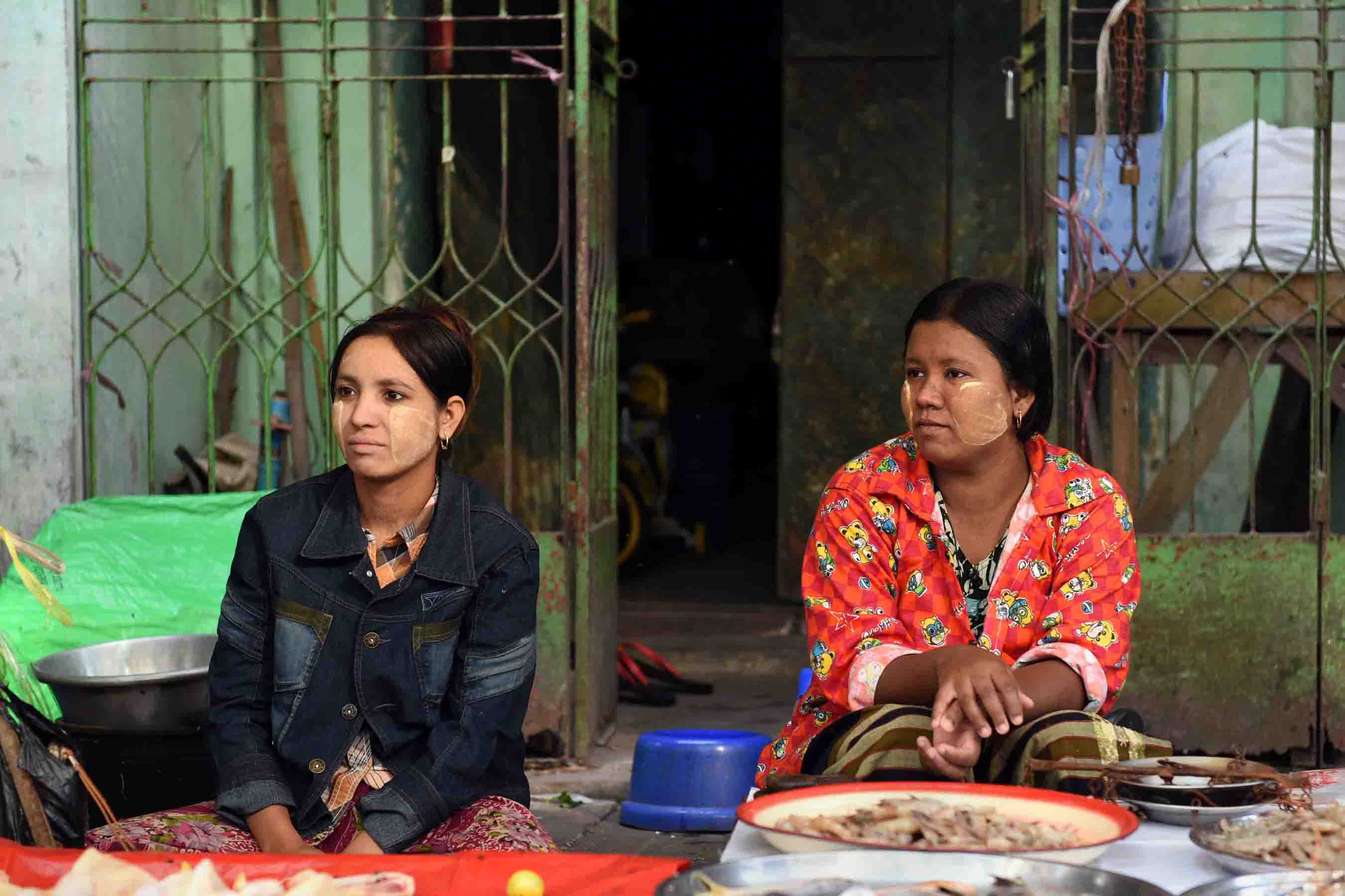 A pair of young fish mongers wearing thanaka waiting for customers. (Photo: Naomi Hellmann)