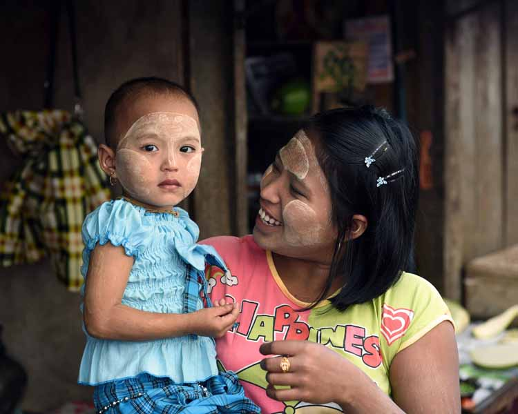 A mother smiles holding her daughter at an outdoor produce market in downtown Yangon. (Photo: Naomi Hellmann)