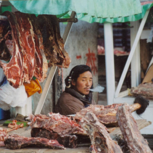A Tibetan man sells yak meat at an outdoor stall in Lhasa. (Photo: Naomi Hellmann)