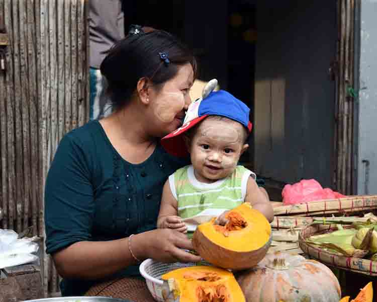 Selling pumpkins and shelling peas at a market in downtown Yangon. (Photo: Naomi Hellmann)