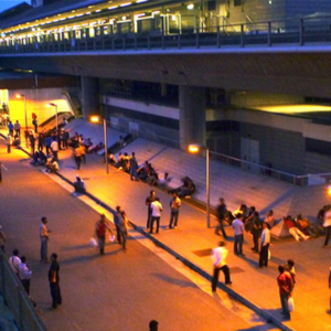 A typical view of Boon Lay MRT station on a weekend night with mostly Bangladeshi men socializing in groups, right under the subway tracks. (Photo: Junjia Ye)