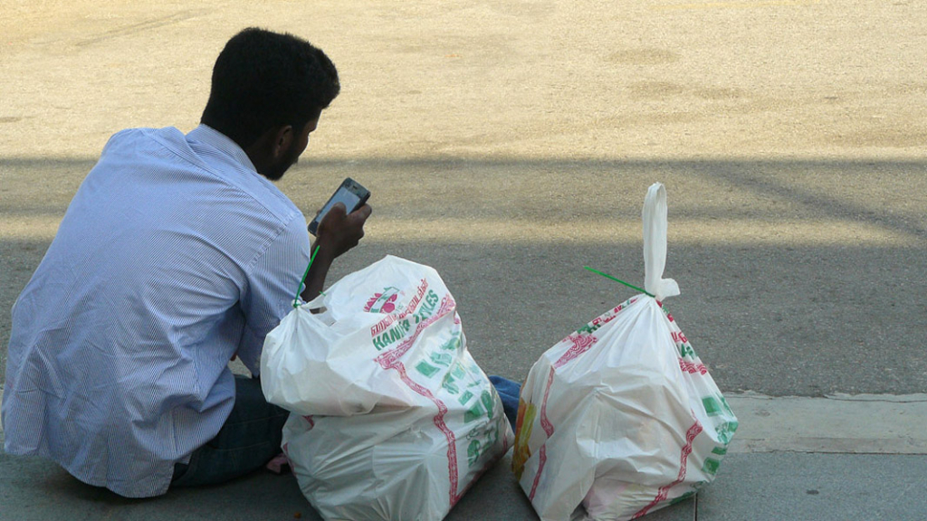An Indian migrant, sits on the sidewalk outside the train (MRT) station texting on his mobile phone. It is a popular meeting spot, especially in the evenings and on weekends. Bags of shopping from Little India could contain gifts for family back home, or groceries for the week. (Photo: Laavanya Kathiravelu)