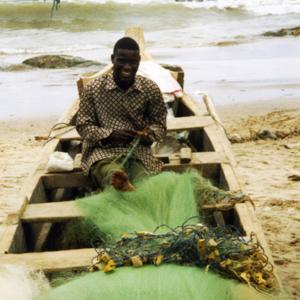 Fisherman repairing his net (Winneba, Ghana). (Photo: Boris Nieswand)