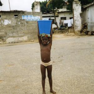 Girl carrying a bucket of water (Winneba, Ghana). (Photo: Boris Nieswand)