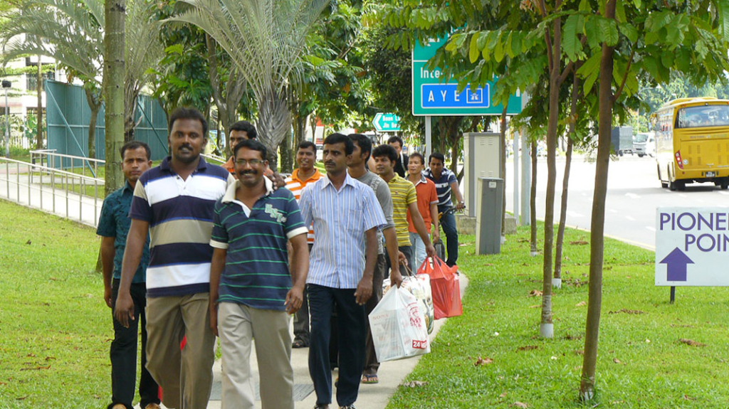 The walkway that runs parallel to government-built public housing is part of the route that low wage migrants take from their dormitories to the train station. Although the passage through this middle class space is part of everyday routines, interaction between these two groups of residents is rare. (Photo: Laavanya Kathiravelu)