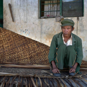An elderly man squats in the entrance of his home, weaving a stiff, flat, straw mat for drying grain on. (Photo: Naomi Hellmann)