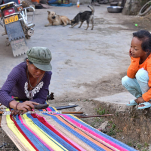 A young girl socializes with a village woman hand weaving a colorful blanket in the open space outside her home. Women often weave outside in late autumn when the air is still warm and dry and the harvest is almost over. (Photo: Naomi Hellmann)