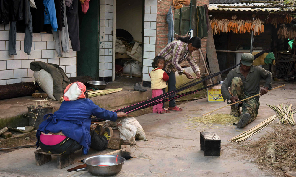 A woman and young child socialize with a neighbor weaving a cloth shoulder bag and her husband, who is splitting thin strips of bamboo with a handheld scythe, in the space outside their home. (Photo: Naomi Hellmann)