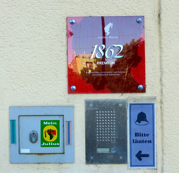 """Entrance to the Julius Meinl company in Julius-Meinl-Gasse, which became one of the most important coffee manufacturer and retailer during the Habsburg Monarchy. A sticker of the initiative """"Mein Julius"""" ('My Julius') challenges the racial stereotypes of the company's logo depicting a black child servant wearing a fez. (Photo: Annika Kirbis)"""