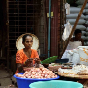A Hindu woman of south Asian descent selling garlic and onions at a bustling morning market. During the colonial era, the British government waived ferry fees to encourage labor migration from India into Burma's fallow delta region. Today, Yangon remains a diverse city with trade frequently divided along ethnic lines. (Photo: Naomi Hellmann)
