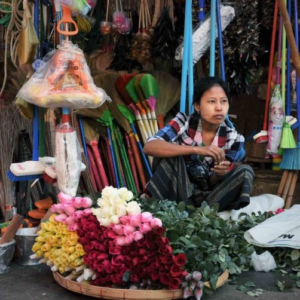Fresh roses for sale from a flat woven bamboo receptacle on the sidewalk in front of a stall with assorted household goods. (Photo: Naomi Hellmann)
