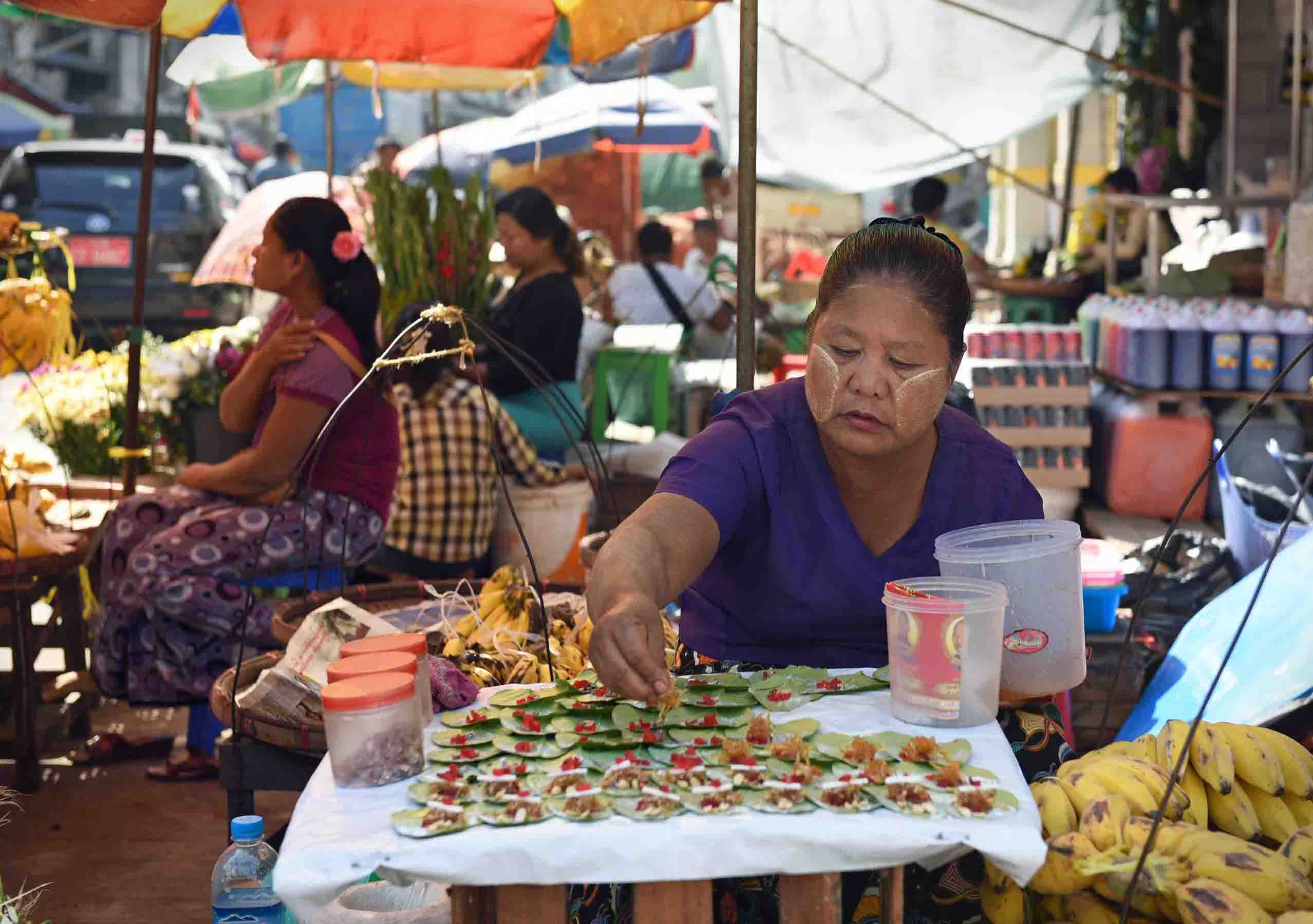 Making paan, a Burmese snack with areca nut wrapped in betel leaves. (Photo: Naomi Hellmann)