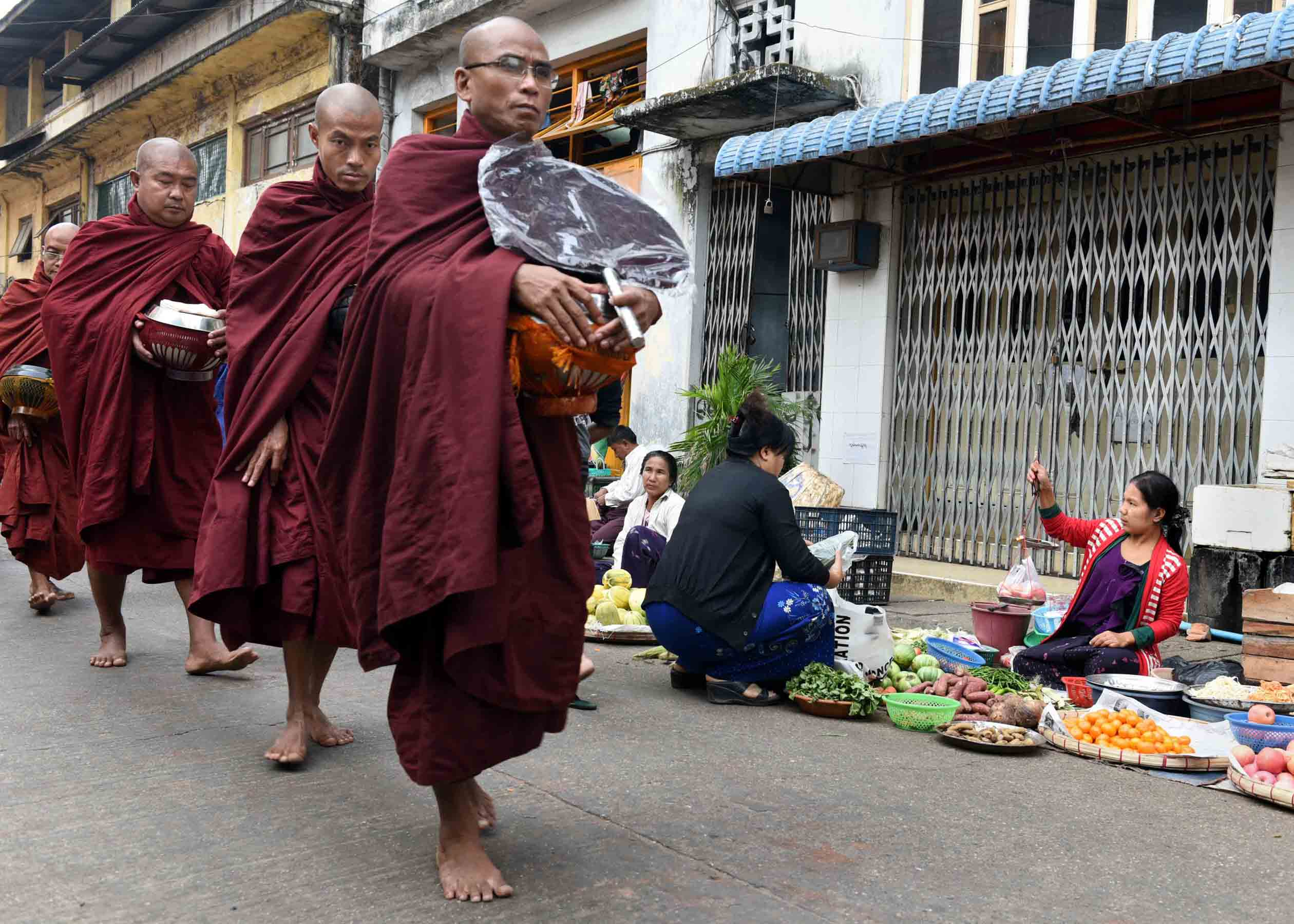 Buddhist monks in crimson robes walk through the streets of Yangon barefoot each morning collecting food, money, and other material offerings from people and bestowing brief prayers in exchange. (Photo: Naomi Hellmann)